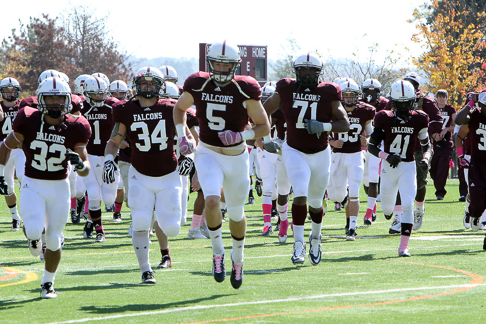 The Fighting Falcons football team runs onto Duvall-Rosier Field for its Oct. 13
